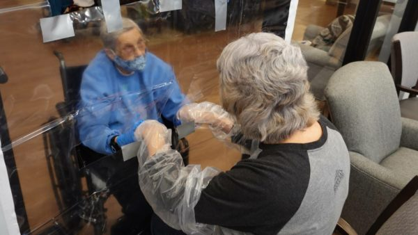 Two women wear gloves and hold hands through holes cut in a clear plastic sheet.