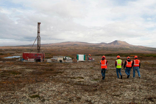 A group of workers in safety vests survey the tundra with a work camp in the background