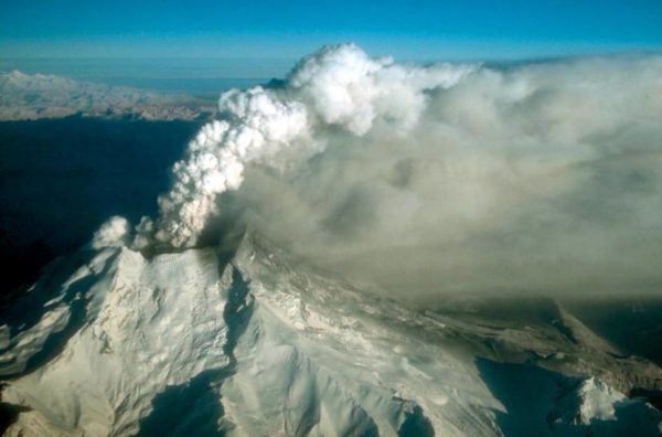 A snow covered mountain erupts