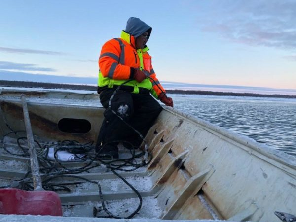 A man sits at the back of the boat navigating through ice in twilight
