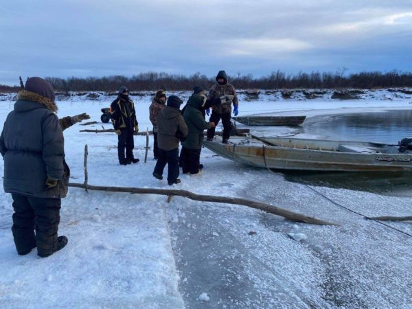 People stand around a skiff on some shore ice