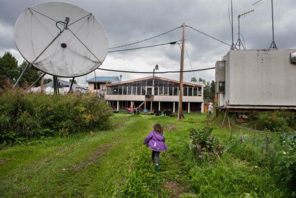 A girl runs toward a home through grazz