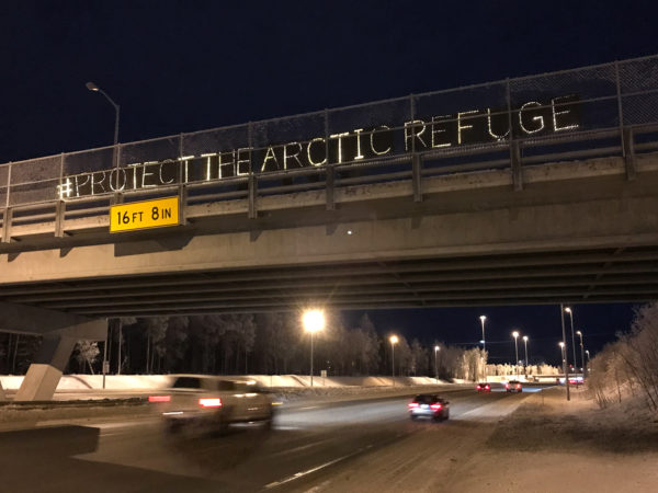 "light-boards spell out ""#ProtectTheArcticRefuge"" over a highway"