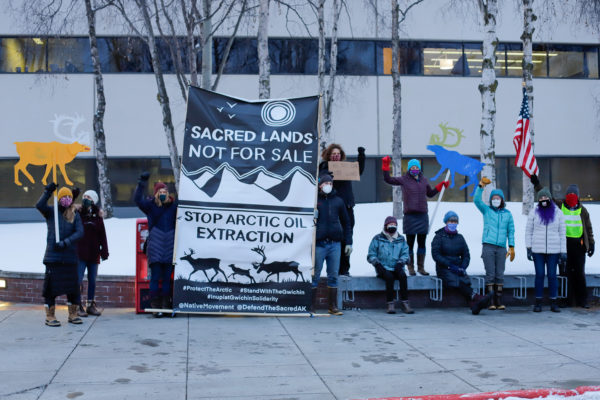 """a group of people standing with a sign that reads """"sacred lands not for sale; stop arctic oil extraction"""""""