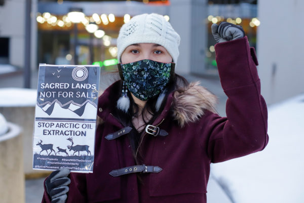 "a person with their fist in the air holds a sign that says ""sacred lands not for sale; stop arctic oil extraction"""