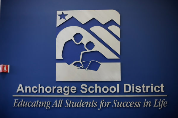 """the logo and text on wall that reads """"Anchorage School District -- Education All Students for Success in Life"""""""
