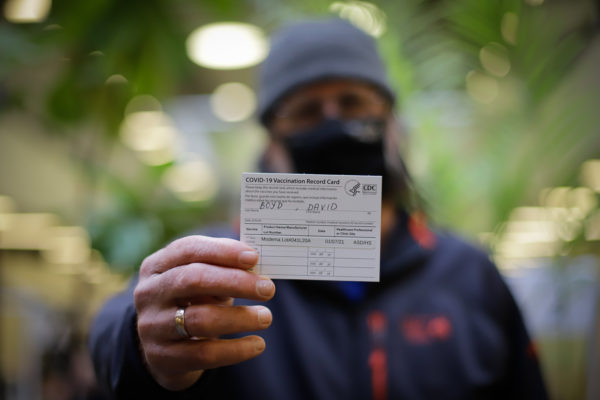 a person holds a Covid-19 vaccination record card