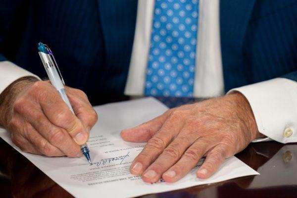 A man's white hands sign a bill