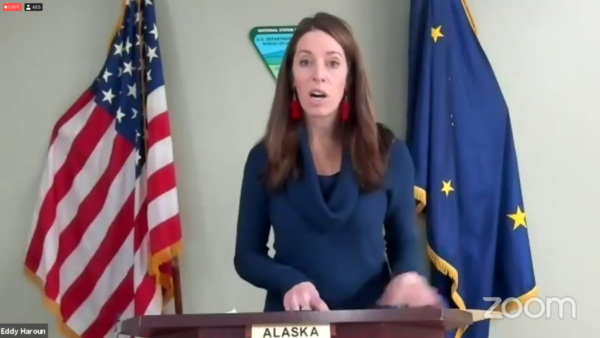 A white woman in a blue shirt speaks at a podium in fronnt of an american and Alaskan flag