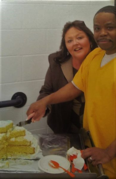 A,black man in a yellow suit holds the hand of a white woman as she cuts a cake in front of some white brick walls
