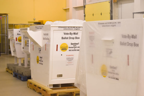 "Large white boxes that read ""Vote by Mail Ballot Drop Box"" sit in a warehouse."