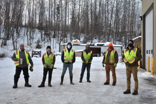Six workers in fluorescent vests stand outside a warehouse in winter