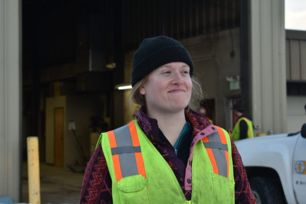A woman wearing a plaid shirt, beanie and fluorescent work vest smiles in front of a warehouse.