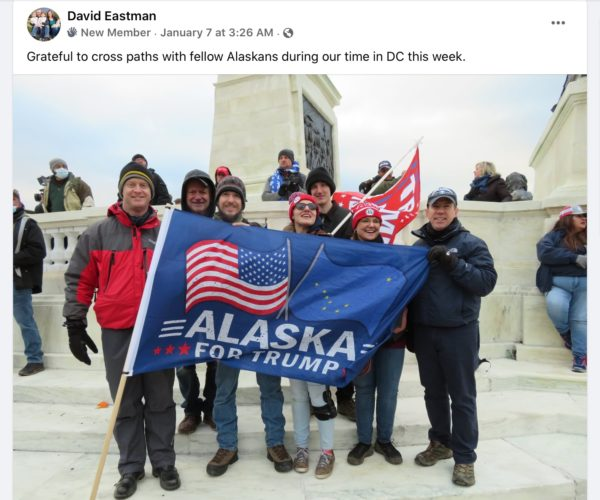 "People stand on marble steps outdoors with flag that says ""Alaska for Trump"""