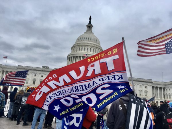A large Trump flag waves in front of the U.S. Capitol