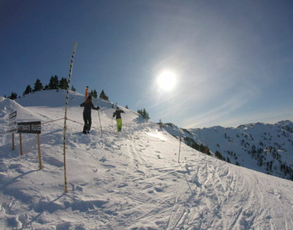 Skiers carry skies on the snow slope on a  sunny day