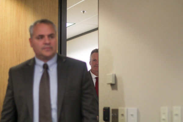 Governor Dunleavy peeks through a door with a man in a suit in the foreground