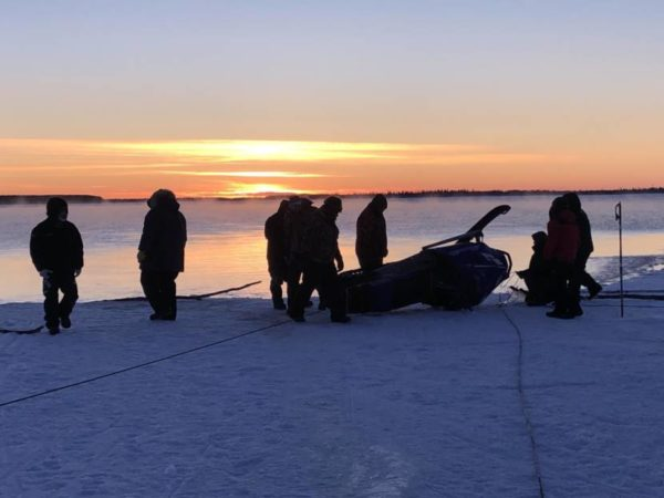 A group of a half dozen people silhouetted in front of a  sunset look over an overturned sno machine on som esnow/ice