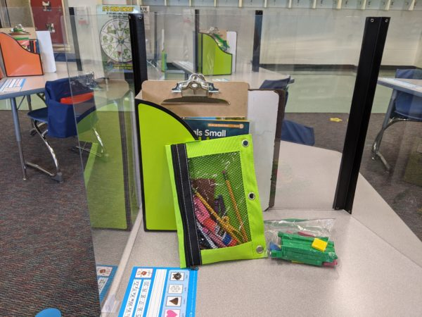 The view of a student desk with a plastic barrier and a folder with school supplies