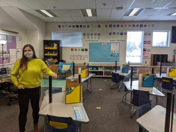A woman stands in a classroom with her arm on a plastic barrier attached to a student's desk