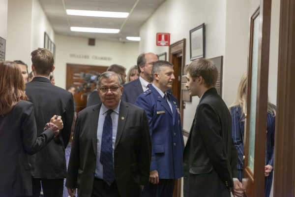 A white man in a suit and blue tie walks throug a crowded corridor
