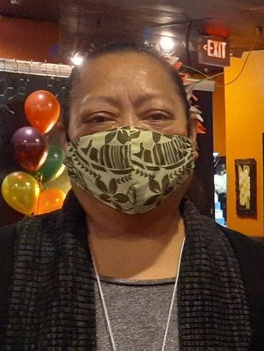A Samoan woman wearing a mask at a party with balloons in the background