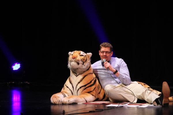 A white man sits on the stage floor with one arm around a stuffed tiger and the other holding a microphone