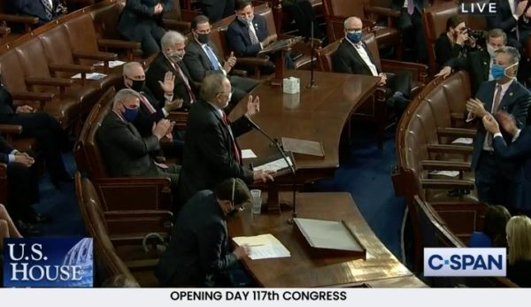 man stands in House chamber, applauded by colleagues