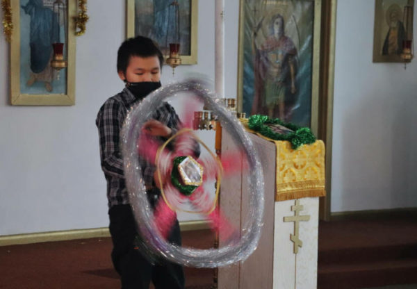 A boy spins a star shaped spinner inside a church wearing a mask