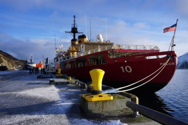 An ice breaker sits at a dock with a ling from the bow
