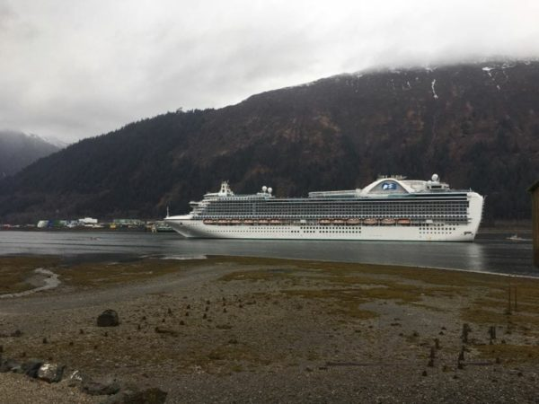 a cruise ship with a fog covered mountain inthe background