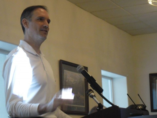 A white man speaks at a podium