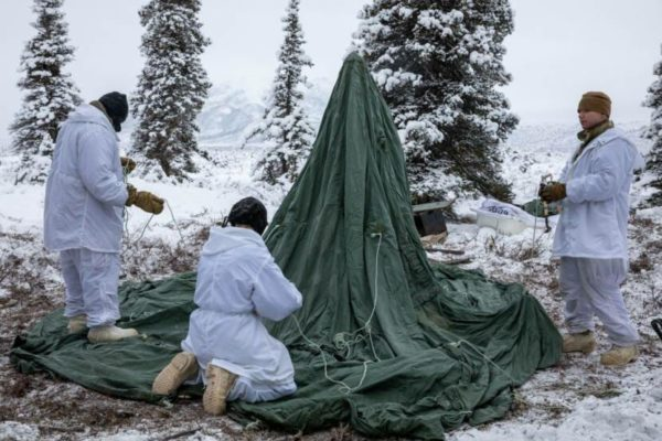 Three men dressed in white oversuits put up a green tent in a snowy landscape near spruce trees