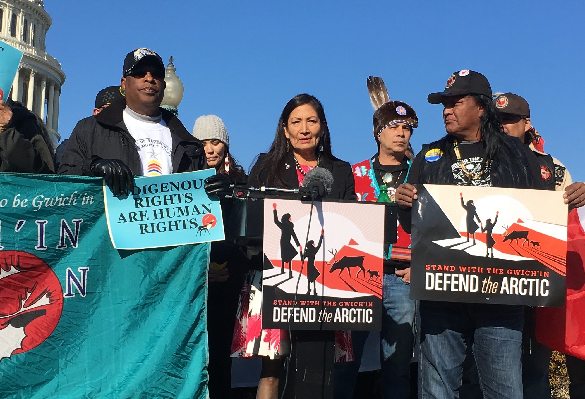 People standing in front of white capitol dome holding banners that say protect the Arctic.