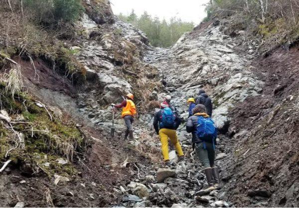 People in rain gear walk up through a muddy gully