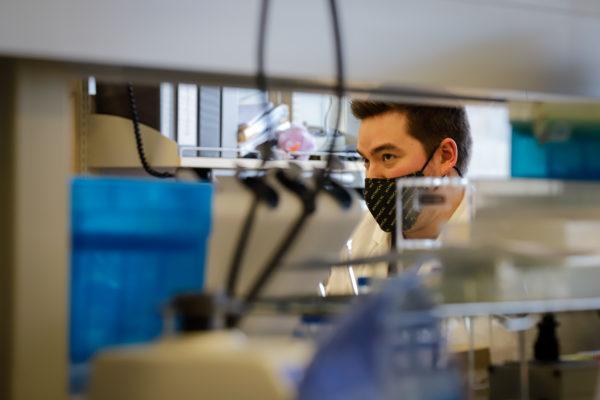 a scientist as seen through lab shelves