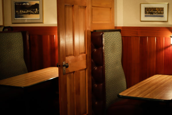 Wooden doors separate two booths.