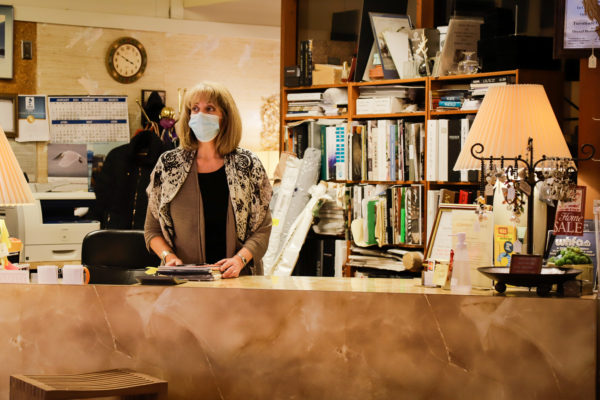 A woman stands behind a counter with a mask on.