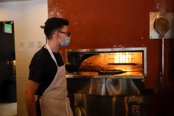 Pizza cooks in a wood-fired oven.