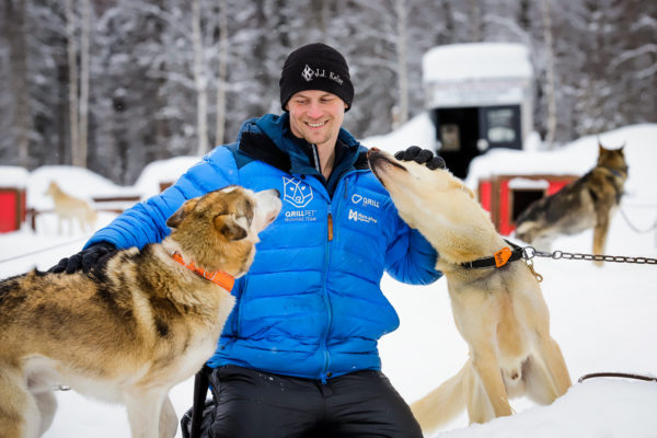 a person in a blue jacket petting his sled dogs