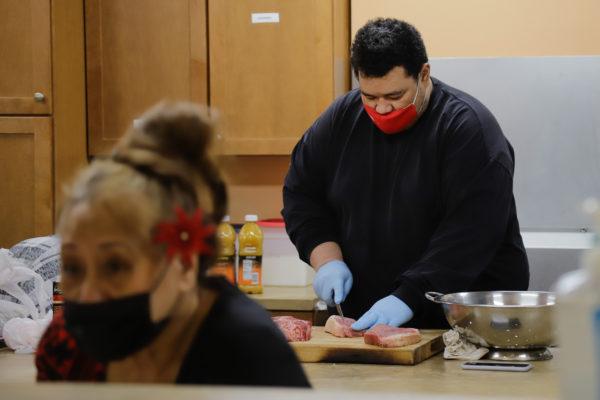 A man in a black shirt cuts food