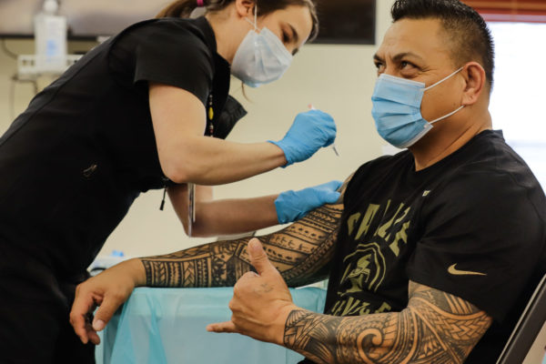 A man with tatooed arms gets a vaccine while giving a shaka symbol