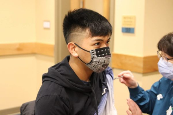 An Alaska native teen with a black mask getting vaccinated