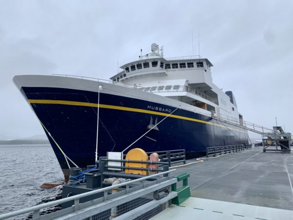 A blue ferry tied up at a dock o na cloudy day as seen from the bow