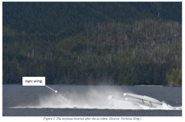 An overturned float plane in front of a mountain side