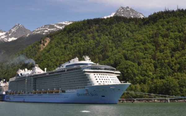 A cruise ship next to a forested hill