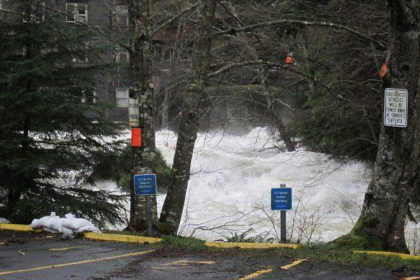 a raging creek behind a parking lot