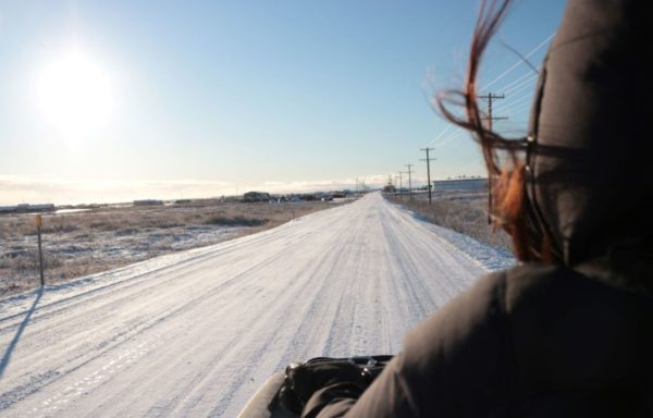Seen from behind, a woman rides down a snowy straight road