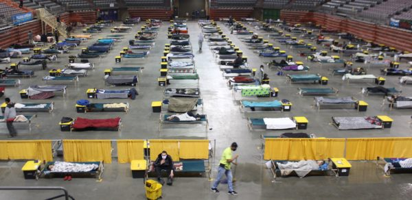 Cots laid out on an arena floor