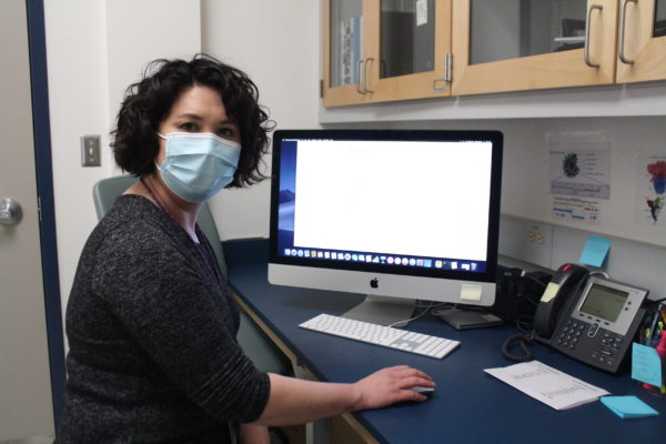 A woman with black, curly hair wearing a mask sitting at a Mac computer